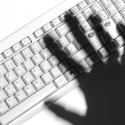 Shadow of a human hand over a computer keyboard