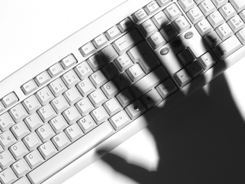 Shadow of a human hand over a computer keyboard