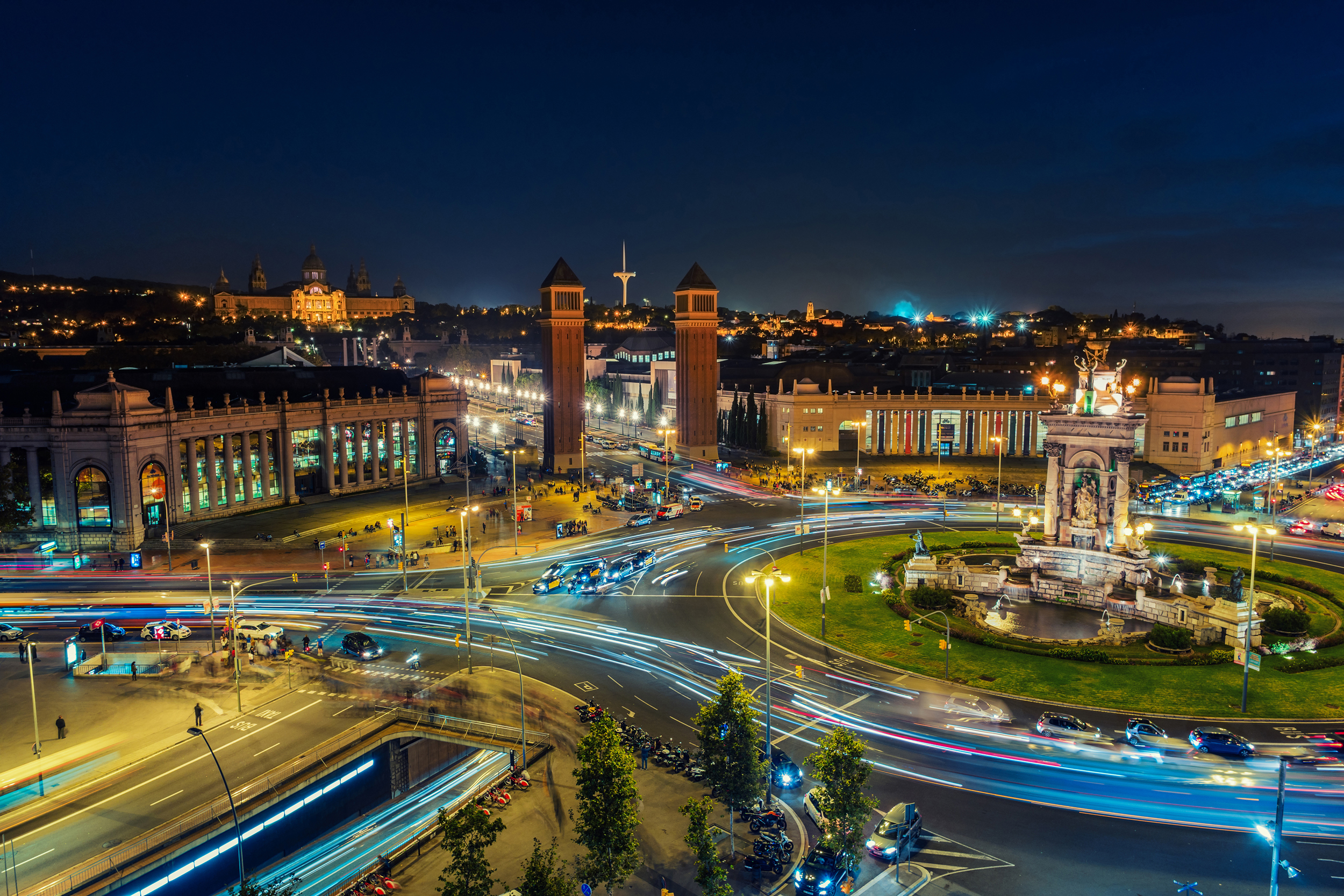 Spanish Square aerial view in Barcelona, Spain at night. This is the famous place with traffic light trails, fountain and Venetian towers, and National museum at the background. Blue sky