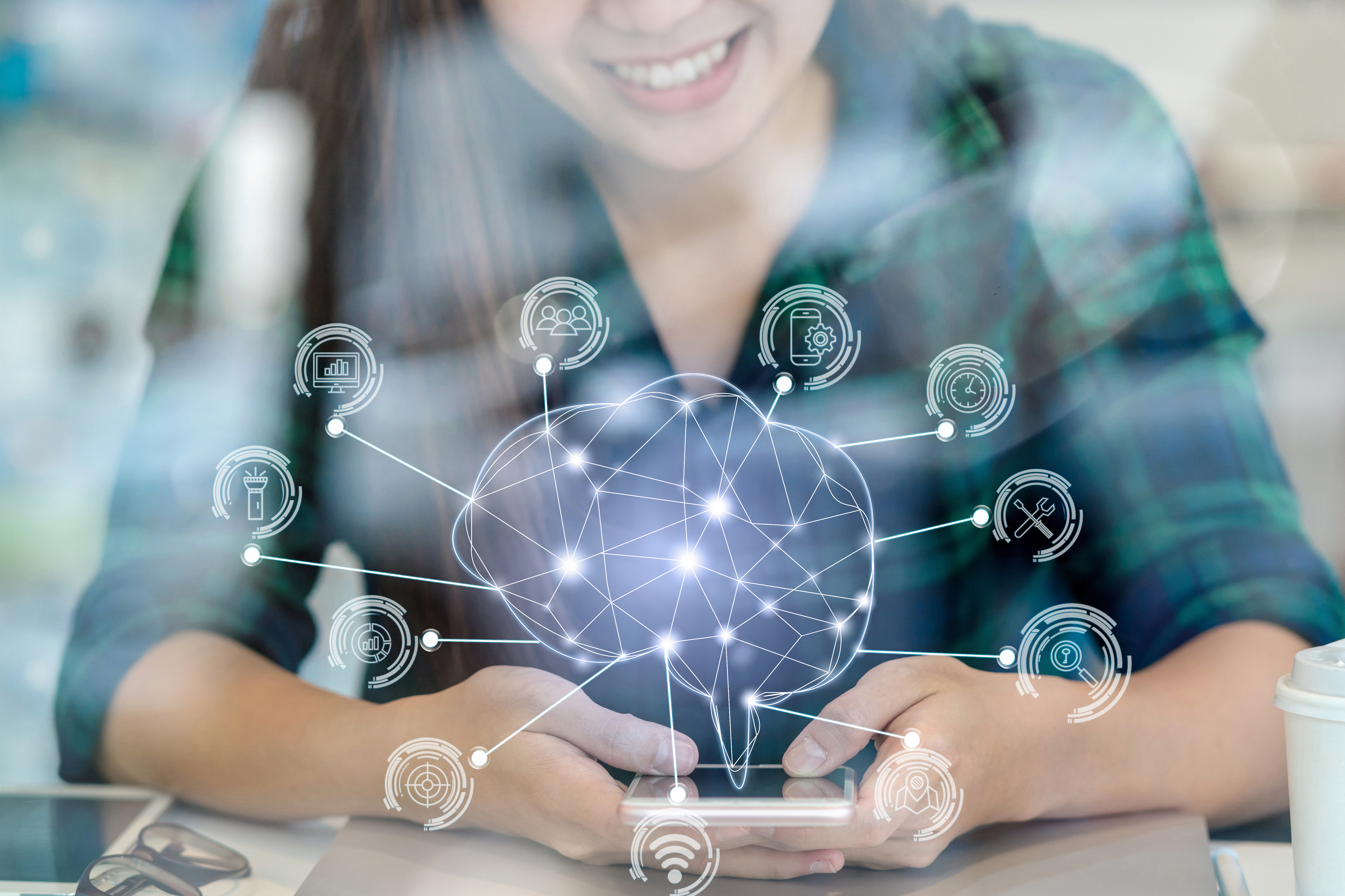 Polygonal brain shape of an artificial intelligence with various icon of smart city Internet of Things Technology over Asian businesswoman hand using the smart mobile phone,AI and business IOT concept, retouch with new product