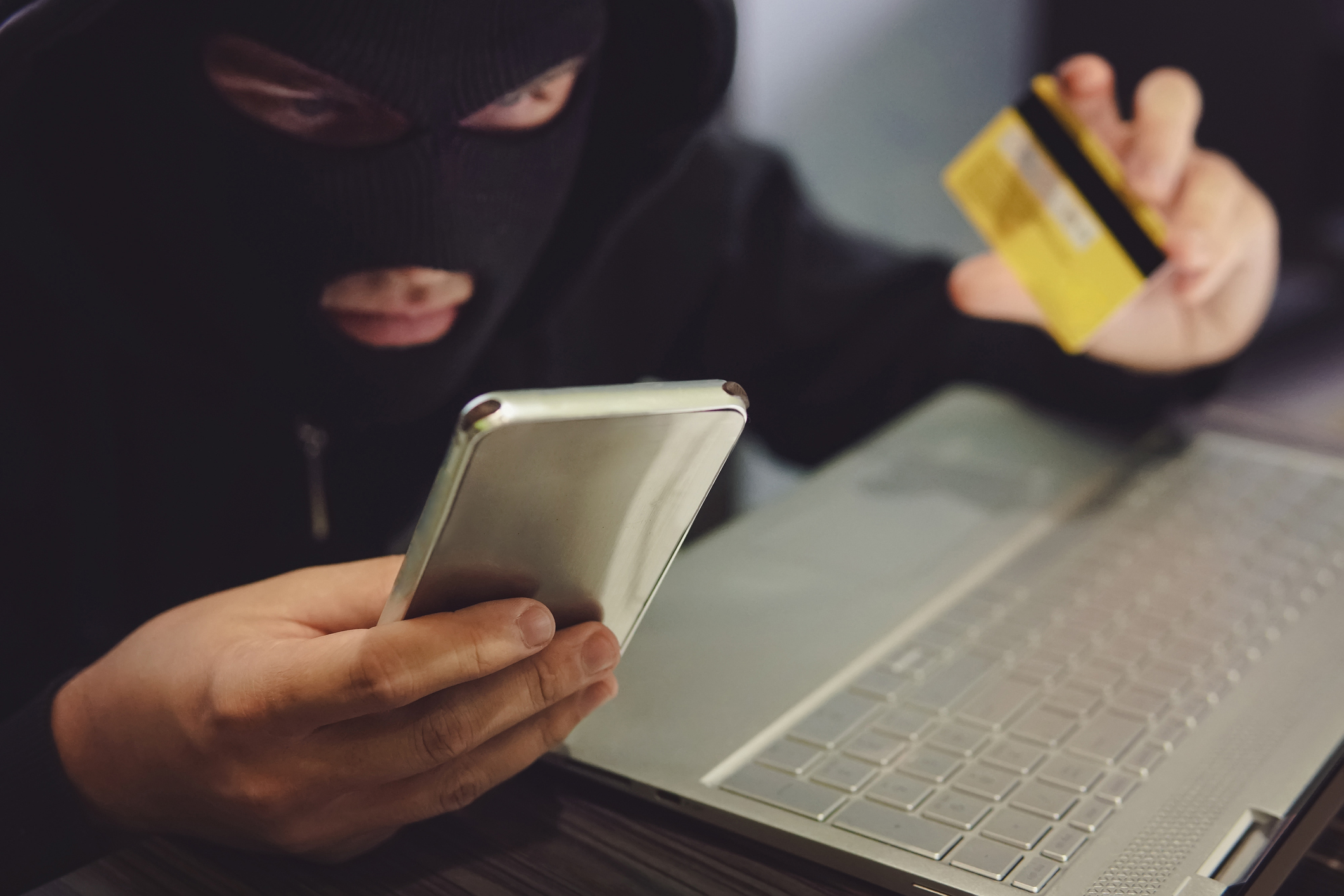 Male hacker in a robber mask uses phone, credit card and laptop in some fraudulent scheme. Cyber thief stole the personal data and credit card information. Hacker uses malware to steal user's money